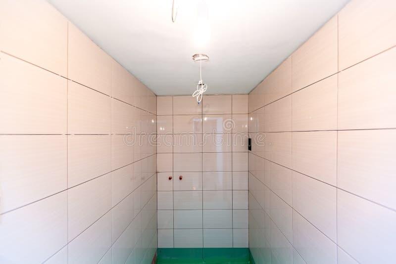 De badkamers met betegelde die muren en de vloer door groene gekleurde waterdicht wordt geschilderd beëindigen materiaal in flat  royalty-vrije stock foto's