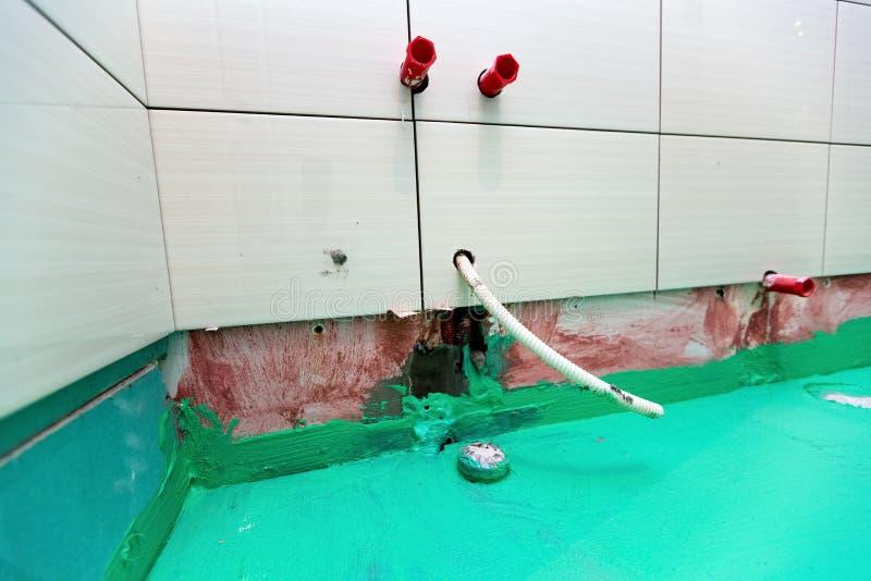 De badkamers met betegelde die muren en de vloer door groene gekleurde waterdicht wordt geschilderd beëindigen materiaal in flat  stock fotografie