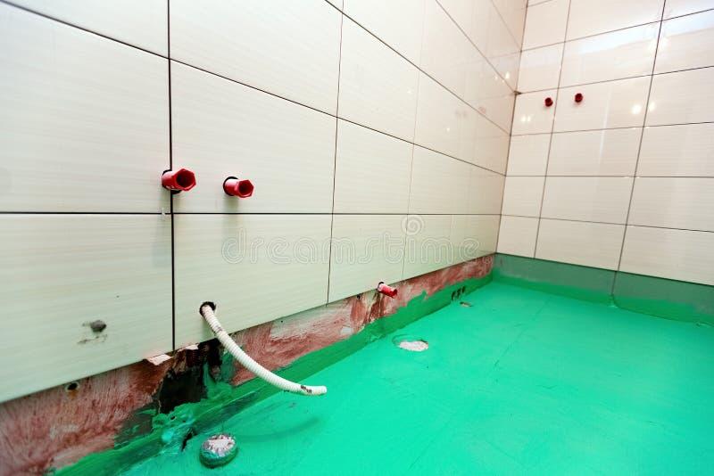 De badkamers met betegelde die muren en de vloer door groene gekleurde waterdicht wordt geschilderd beëindigen materiaal in flat  stock afbeeldingen