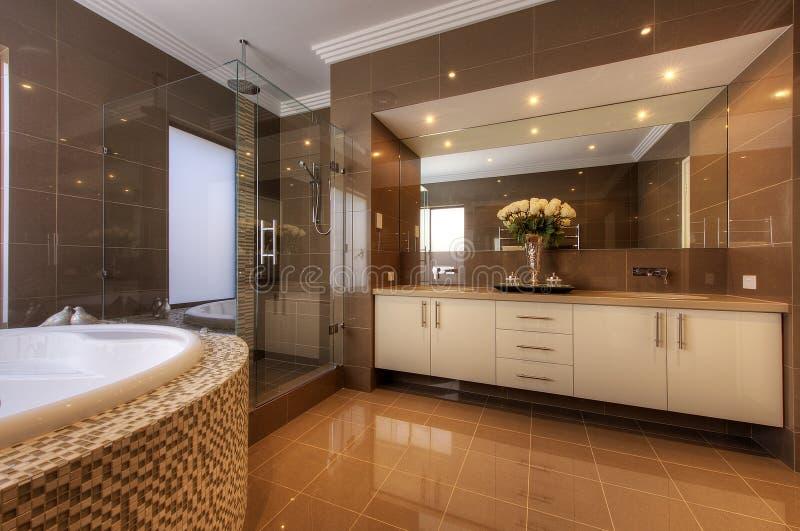 De badkamers van de luxe in modern huis stock afbeeldingen