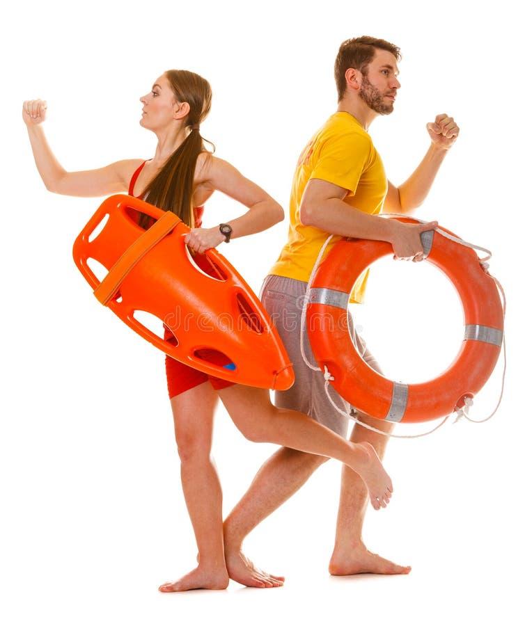 De badmeesters die met redding lopen bellen boei op plicht stock foto