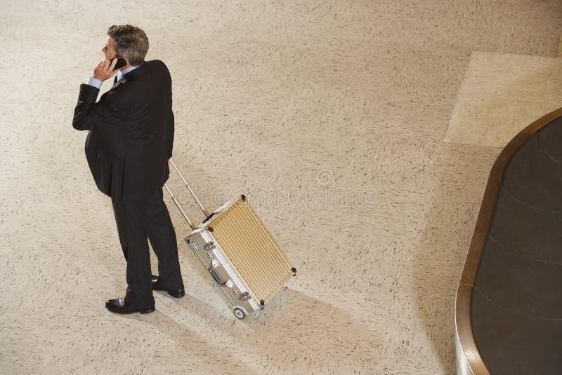 De Bagagecarrousel van zakenmanwith suitcase by in Luchthaven stock afbeeldingen