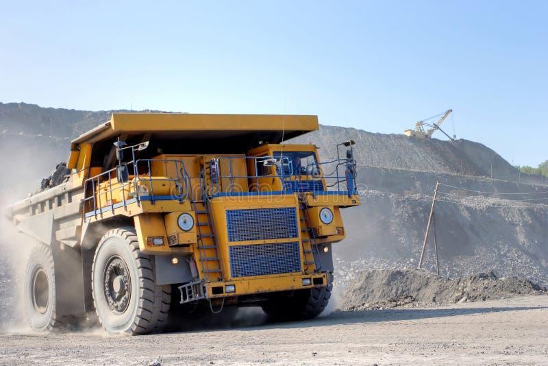 De baggermachine laadt de vrachtwagensteenkool De vrachtwagen die steenkool vervoert royalty-vrije stock foto