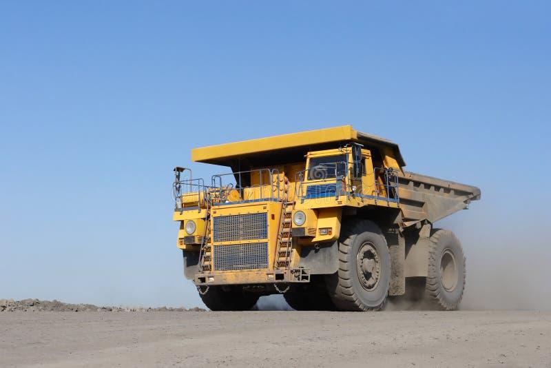De baggermachine laadt de vrachtwagensteenkool De vrachtwagen die steenkool vervoert stock foto's