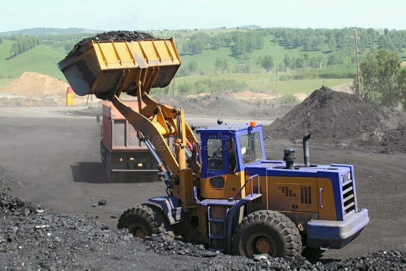 De baggermachine laadt de vrachtwagensteenkool Steenkoollader stock afbeeldingen
