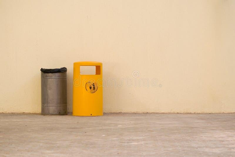 De bak van het metaalafval door de kant van gele plastic afvalbak stock afbeelding