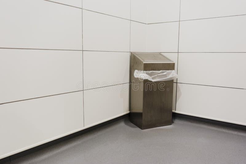 De bak van het metaalstaal en witte plastic zak onder klep in hoek tegen neutrale bleke tegels in het ziekenhuis stock fotografie
