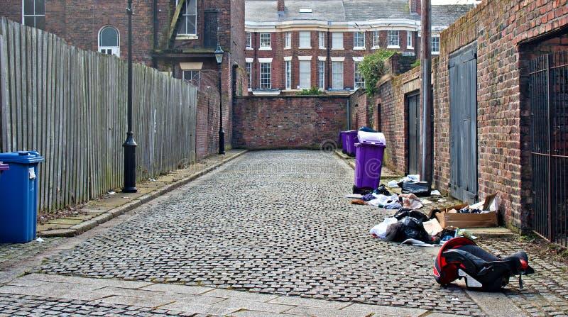 De bakken van het vuilnis in smalle steeg worden opgesteld die royalty-vrije stock foto