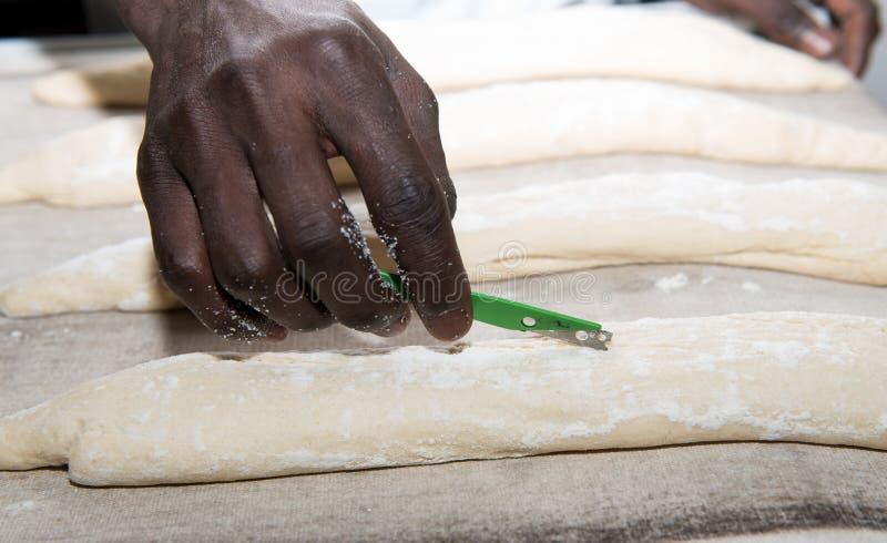 De bakker bereidt brooddeeg voor stock foto's