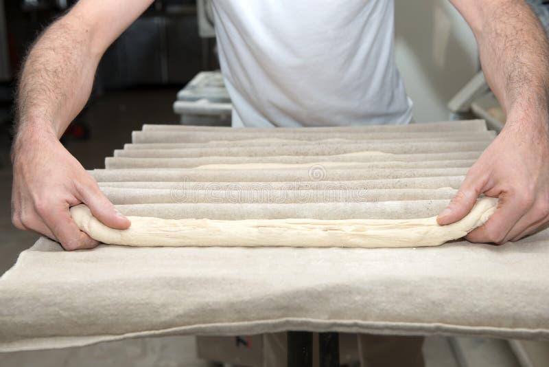 de bakker bereidt brooddeeg voor stock afbeelding