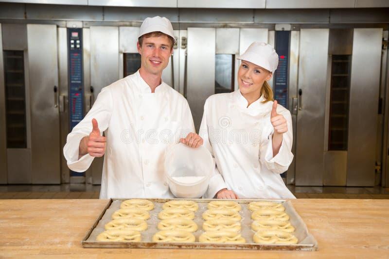 De bakkers in Bakkerij met dienblad van pretzels het geven beduimelt omhoog stock foto