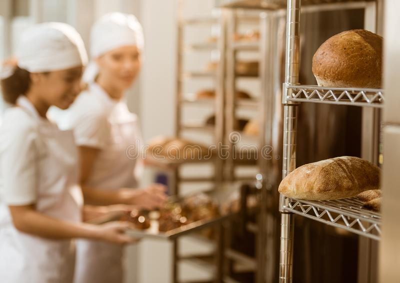 de bakkers die bij baksel werken vervaardigen met verse broden van brood liggend op planken stock foto's