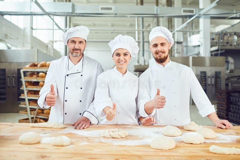 De bakkers hieven omhoog hun duimen in bakkerij op stock foto's