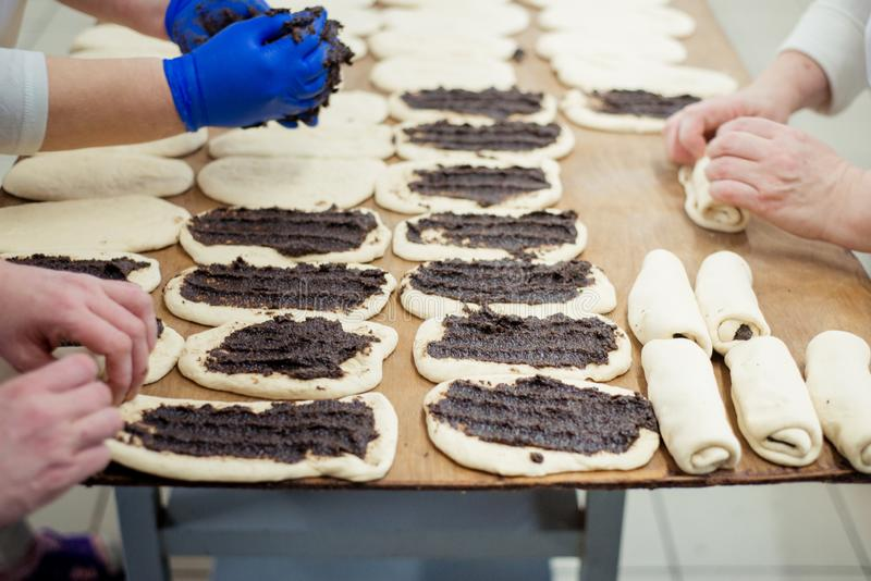 De bakkers maken broodjes van deeg met papaver het vullen stock afbeelding