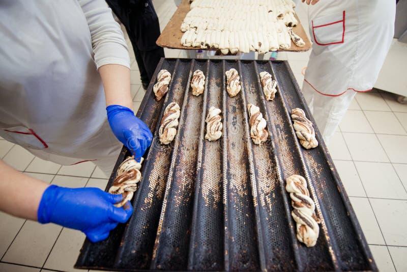 De bakkers maken de zoete broodjes van deeg op een bakseldienblad op stock afbeeldingen