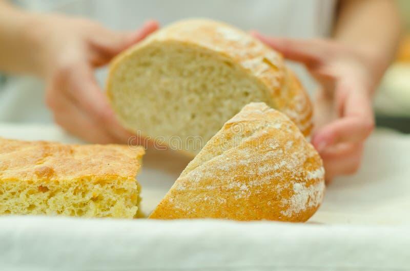 De bakkershanden die de helft plaatsen snijden brood van brood op witte plaat naast andere broden royalty-vrije stock afbeeldingen