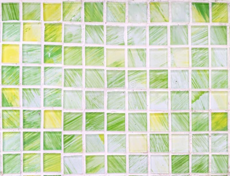 De baksteenpatroon van de close-upoppervlakte bij abstracte groene en gele tegel op de geweven achtergrond van de badkamersmuur stock fotografie
