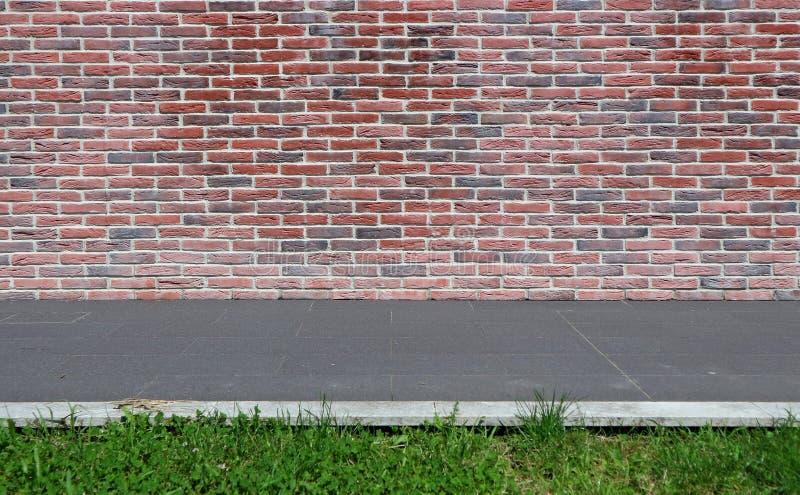 De bakstenen muur met rode en zwarte kleuren, een grijze steen betegelt stoep en een strook van gras achtergrond voor exemplaarru royalty-vrije stock foto