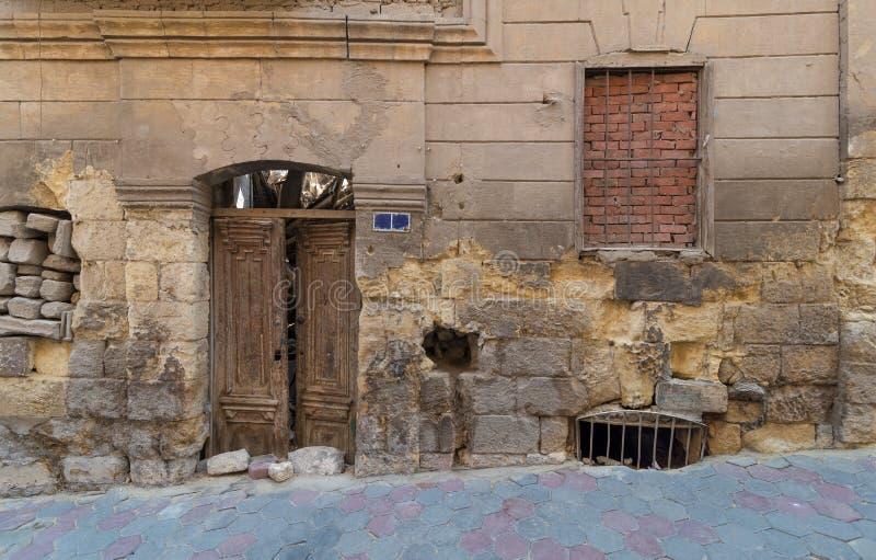 De bakstenen muur van de Grungesteen met Gebroken houten deur en gesloten gebroken venster, Kaïro, Egypte royalty-vrije stock foto's