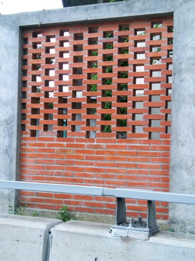 De bakstenen tonen en cementeren muur naast weg stock foto
