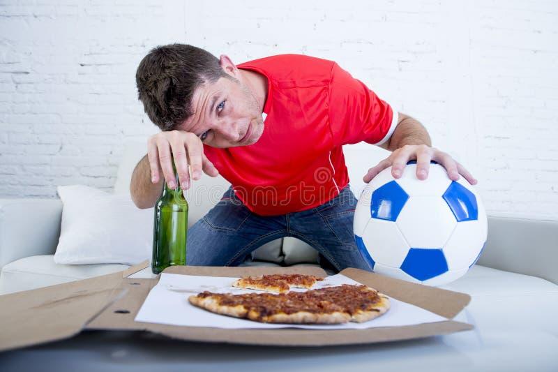 De bal van de mensenholding en bierfles het letten op voetbalspel op teneergeslagen droevig van TV en teleurgesteld voor mislukki royalty-vrije stock fotografie