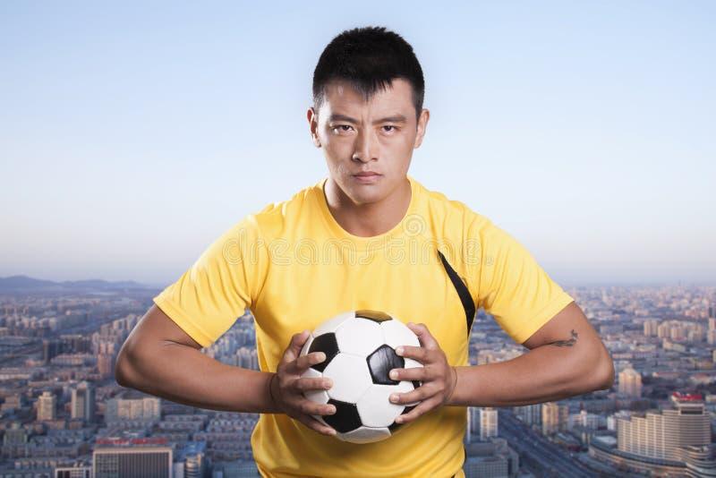 De bal van de voetballersholding aan borst, cityscape achtergrond royalty-vrije stock fotografie