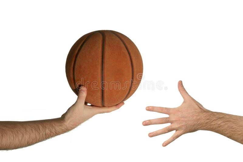 De bal van het basketbal van hand aan hand stock fotografie