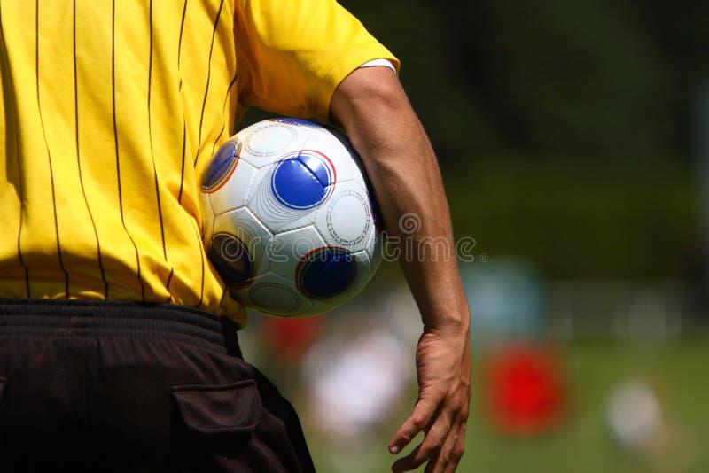 De bal van het de holdingsvoetbal van de scheidsrechter royalty-vrije stock fotografie