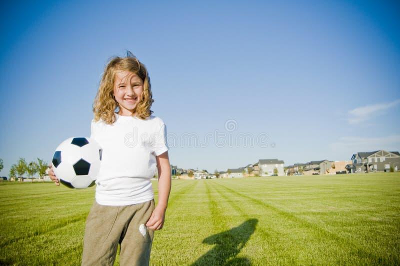 De bal van het de holdingsvoetbal van het meisje het glimlachen royalty-vrije stock foto