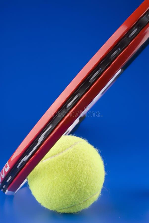 De tennisbal is naast een deel van een tennisracket royalty-vrije stock afbeelding