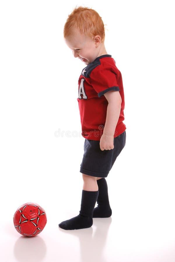 De bal van het voetbal het schoppen de jeugd royalty-vrije stock afbeeldingen