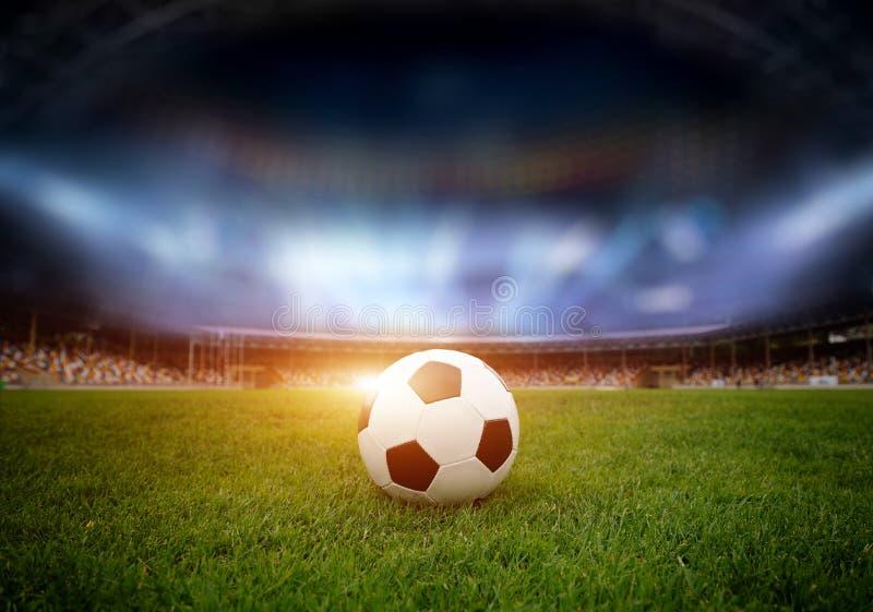 De bal van het voetbal op het gebied van stadion stock afbeelding