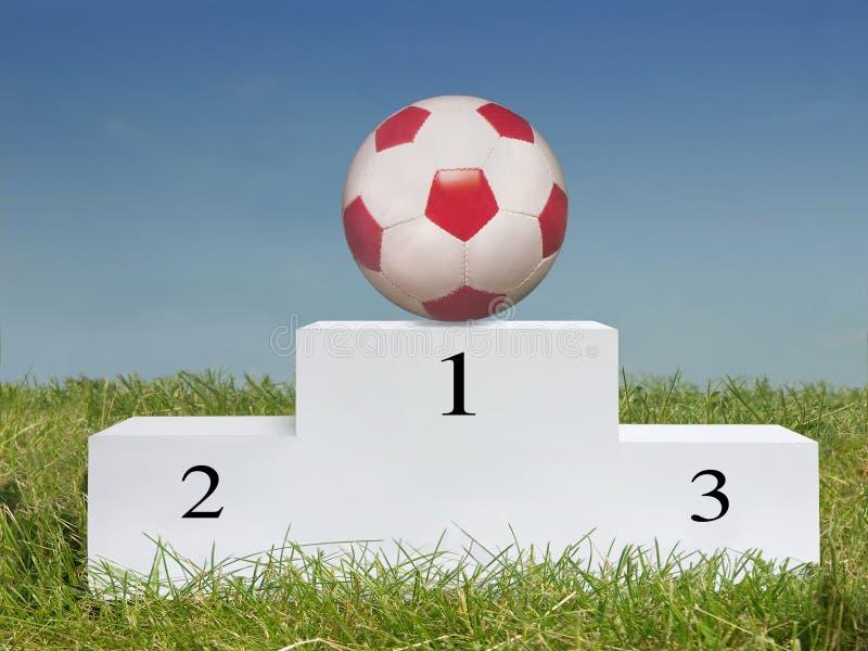 De bal van het voetbal op podium stock afbeelding