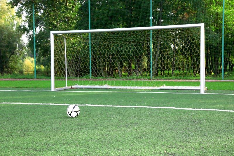 De bal van het voetbal op stadiongebied stock afbeeldingen