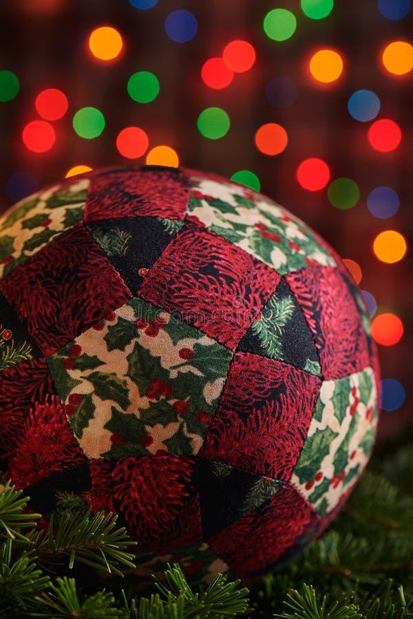 De bal van de Kerstmisdecoratie van stukken stoffen op takken van nette, donkere kleurrijke bokehachtergrond die wordt genaaid royalty-vrije stock afbeeldingen