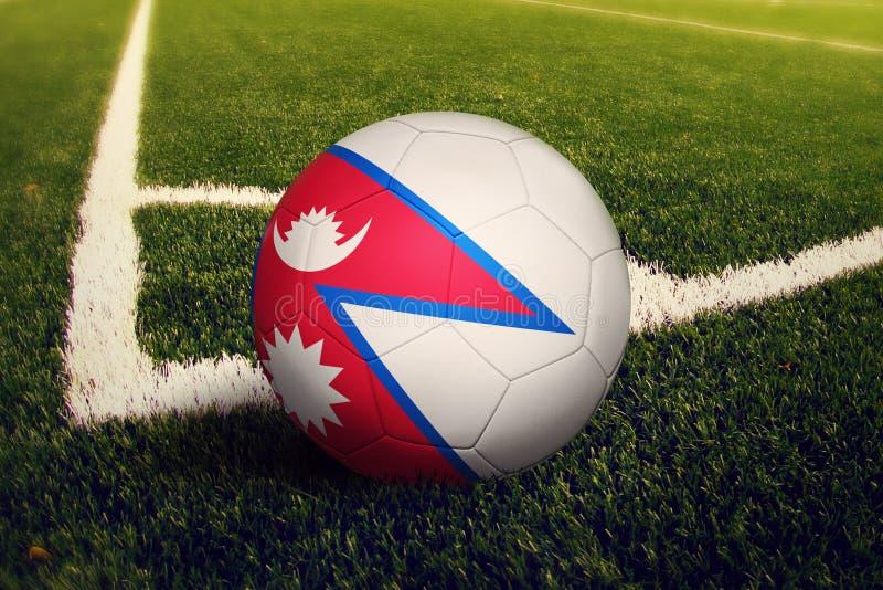 De bal van Nepal op de positie van de hoekschop, de achtergrond van het voetbalgebied Nationaal voetbalthema op groen gras stock afbeelding
