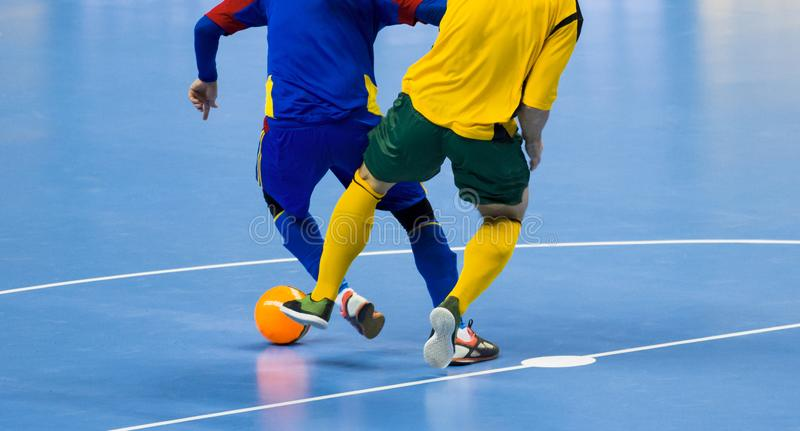 De Bal van voetbalfutsal en mensenteam Binnenvoetbalsporthal stock afbeelding