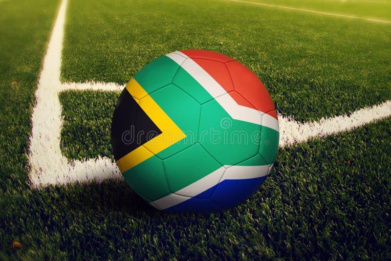 De bal van Zuid-Afrika op de positie van de hoekschop, de achtergrond van het voetbalgebied Nationaal voetbalthema op groen gras stock afbeelding