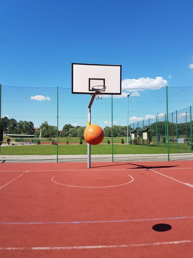 De bal vliegt in de basketbalring op een zonnige en duidelijke dag Basketbalhof in openlucht met kunstmatige oppervlakte holding royalty-vrije stock afbeeldingen