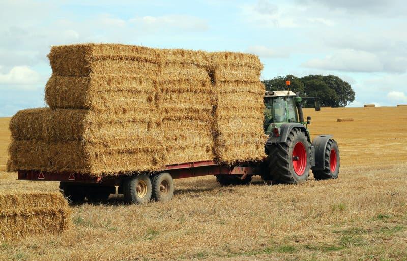 De balen, de tractor en de aanhangwagen van het stro. royalty-vrije stock fotografie