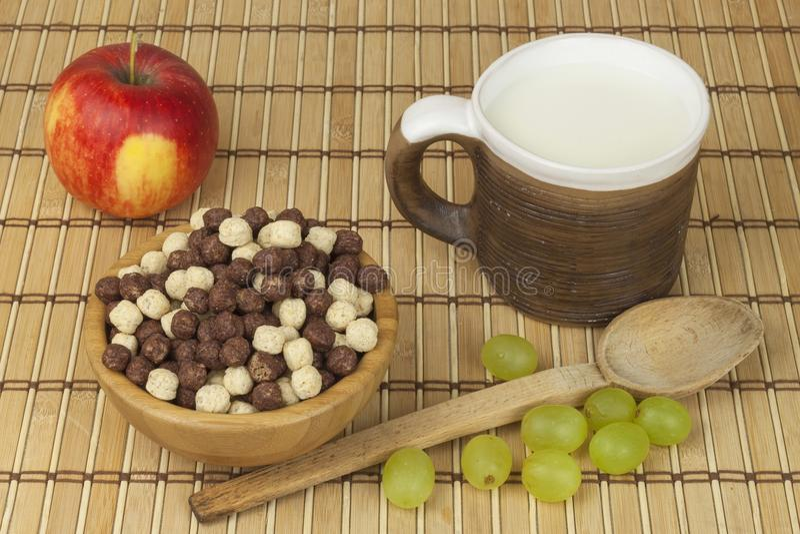 De ballen van het chocoladegraangewas in een kom bamboe Gezond ontbijt met fruit en melk Een dieethoogtepunt van energie en vezel stock foto's