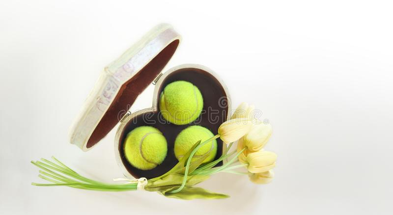 De ballen van het de lay-outtennis van de tennisliefde in doos in vorm van hart met boeket witte tulpen op witte achtergrond Vrou stock foto