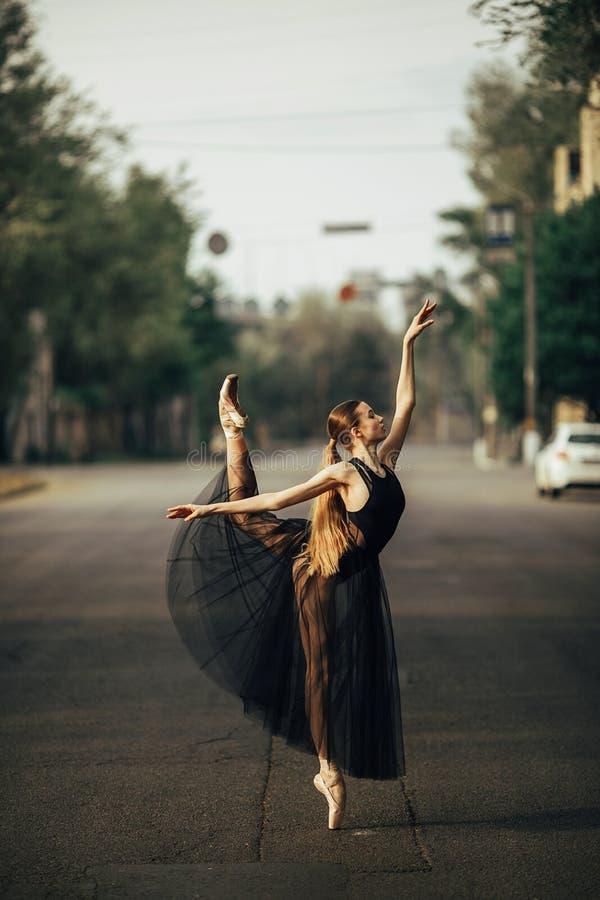 De ballerina die zich in arabesque bevinden stelt tegen de achtergrond van stadsstraat royalty-vrije stock foto's