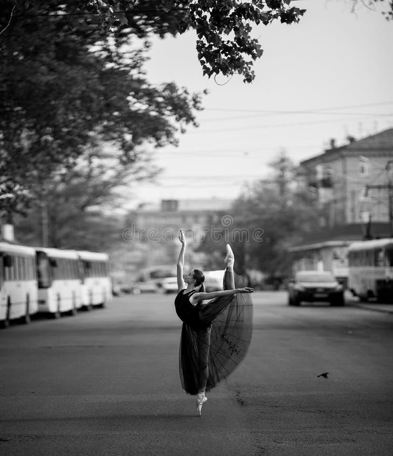 De ballerina die zich in arabesque bevinden stelt tegen de achtergrond van stadsstraat stock foto's