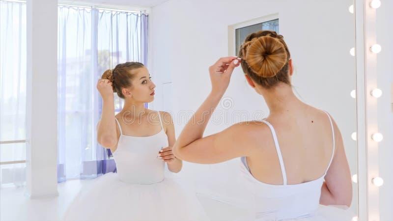 De ballerina doet haar haar die zich voor de spiegel in de klasse van de theaterdans bevinden stock foto