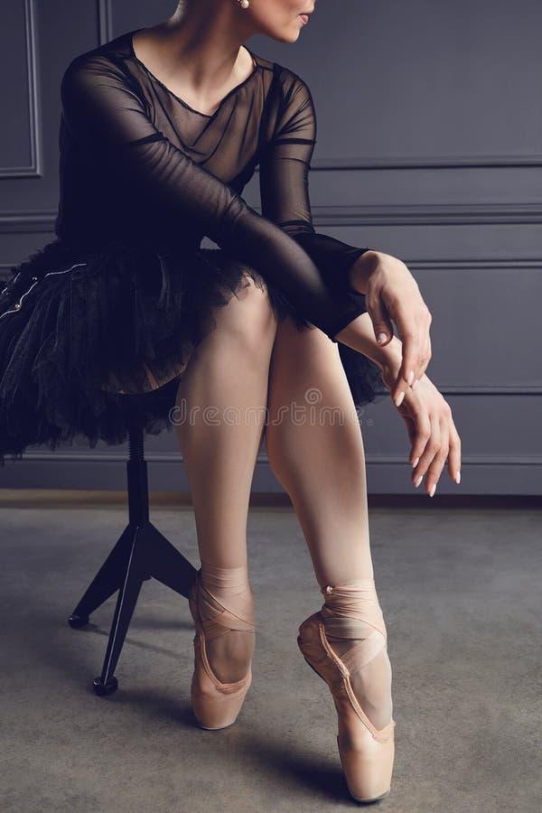 De ballerina in een zwarte tutu zit op een stoel op een zwarte achtergrond stock foto