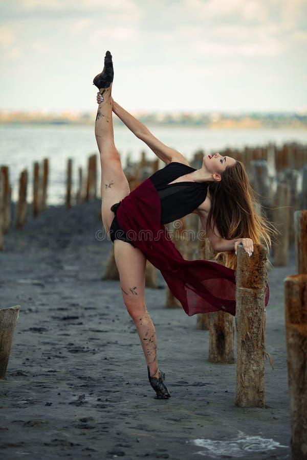 De ballerina in lange kleding danst op strandachtergrond royalty-vrije stock foto