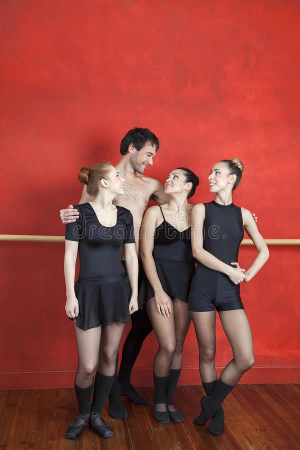 De Ballerina's van trainerstanding arms around in Studio royalty-vrije stock foto