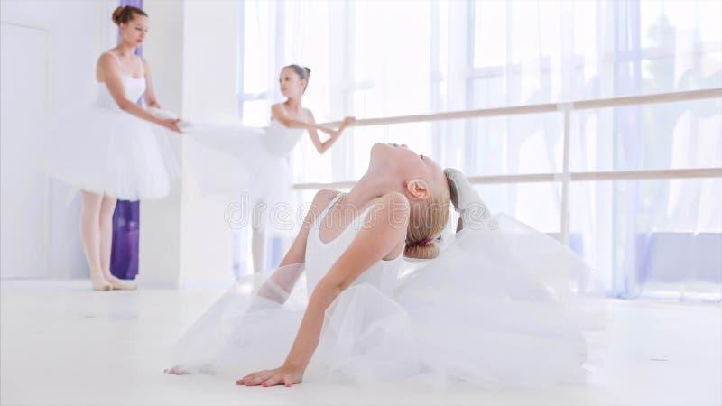 De ballerina van het kindmeisje in witte tutu doet rekoefeningen op balletles royalty-vrije stock afbeeldingen