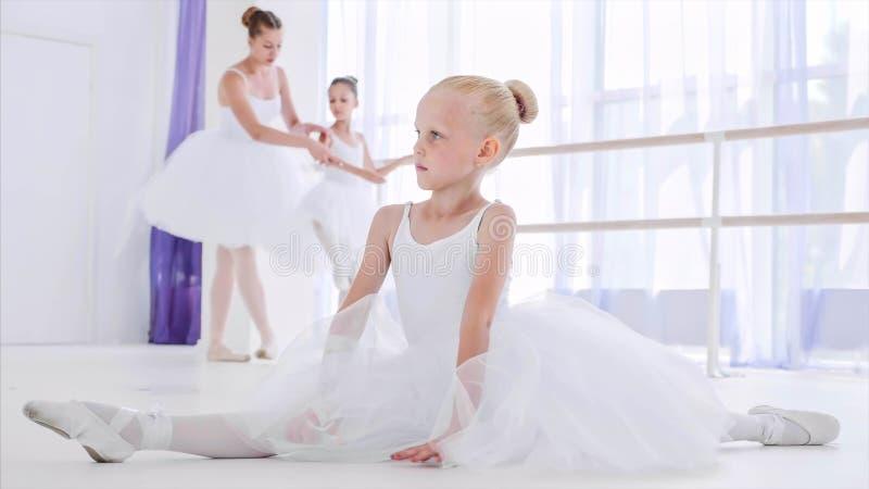 De ballerina van het kindmeisje in witte tutu doet rekoefeningen op balletles stock afbeeldingen